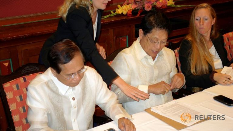 Philippine government negotiators Jesus Dureza (L) and Silvestre Bello sign an indefinite ceasefire agreement with communist rebels at a meeting in Oslo