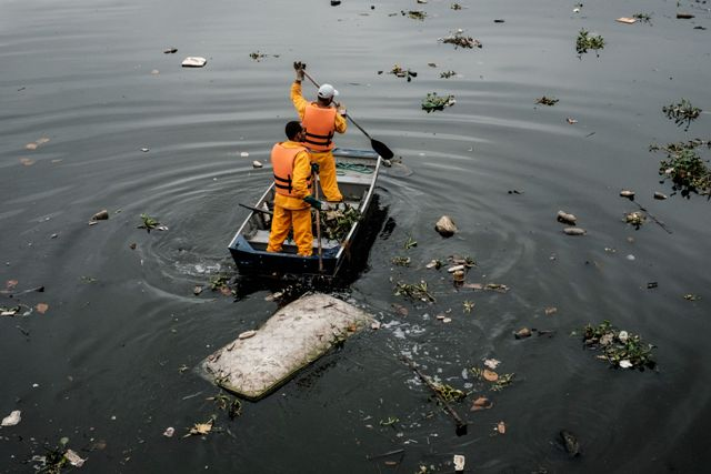 Environment Institute of Rio de Janeiro State (INEA) staffers collect rubbish near Guanabara Bay in Rio