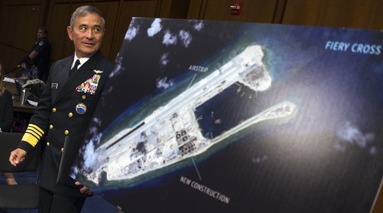 Adm. Harry B. Harris, Jr., U.S. Navy Commander, U.S. Pacific Command walks past a photograph showing an island that China is building on the Fiery Cross Reef in the South China Sea