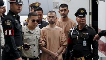 Suspects of last year's Bangkok blast Bilal Mohammed, centre, who is also known as Adem Karadag, and Yusufu Mieraili behind him are escorted by prison officers as they arrive at the military court in Bangkok on Tuesday. (Chaiwat Subprasom/Reuters