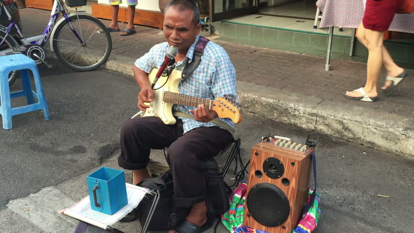 Blind artist playing electric guitar with mini speaker in Chiang Rai.