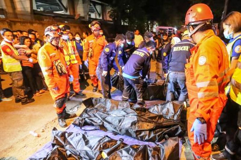 Rescue workers gather bags containing dead bodies of victims of an explosion at a night market in Davao City