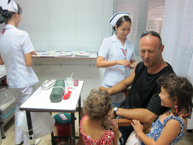Family gets vaccination at travel clinic in Thailand.