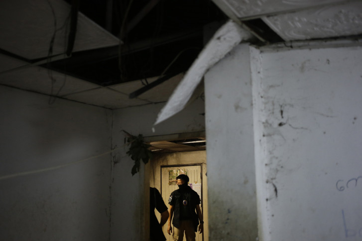 Thailand's Department of Special Investigation searches a room at the workers' living quarters during a raid on a shrimp shed in Samut Sakhon, Thailand. (AP Photo/Dita Alangkara)