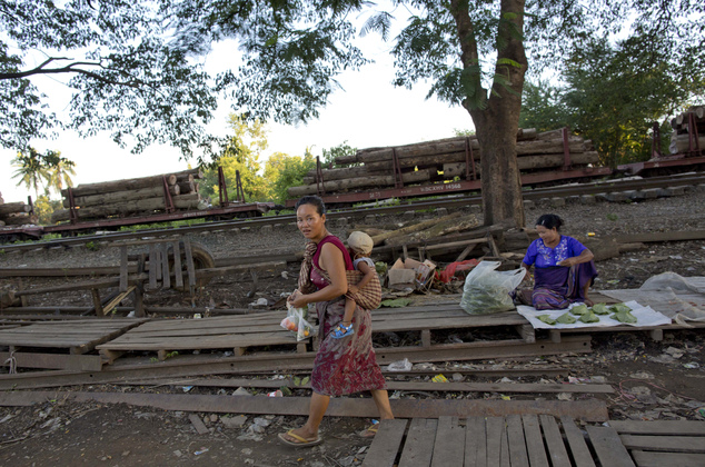 In this June 27, 2016, photo, tree trunks are loaded to train carriages for transportation in the background of a street market at Wuntho, northern Sagaing division, Myanmar. Myanmar is struggling to stop illegal logging that has erased one-quarter of the country's valuable forests in a generation. (AP Photo/ Gemunu Amarasinghe)