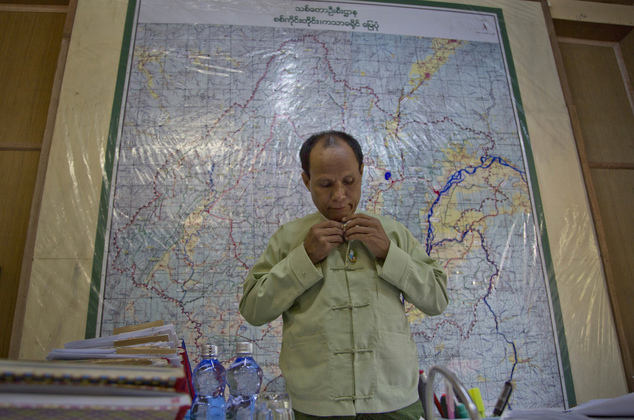 In this  June 28, 2016, photo, government forest commissioner Soe Tint adjusts his jacket at his office in Katha, northern Sagaing division, Myanmar. Soe Tint said his workers are often threatened or even harmed by the illegal loggers and they frequently ask for backup from police. Myanmar is struggling to stop illegal logging that has erased one-quarter of the country's valuable forests in a generation. (AP Photo/ Gemunu Amarasinghe)