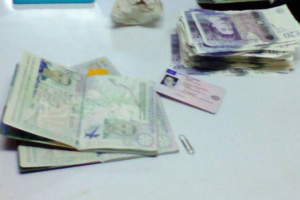 An image shows the passports of the arrested men and forged 20-pound notes