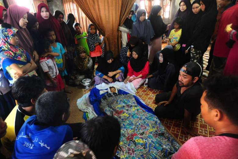 Grieving relatives gather around the body of a four-year-old girl during funeral preparations after she and her father were killed by a blast in front of a school.PHOTO: AFP