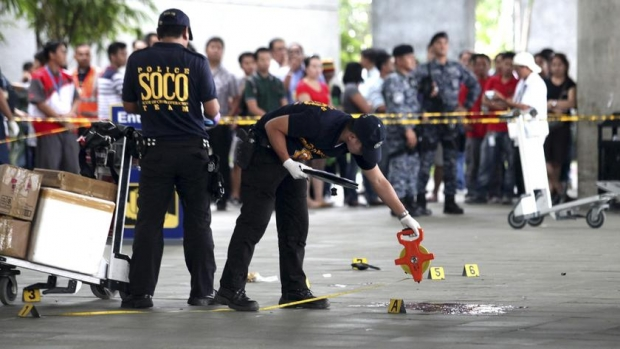 police investigators working at the crime scene after a shooting attack in Manila