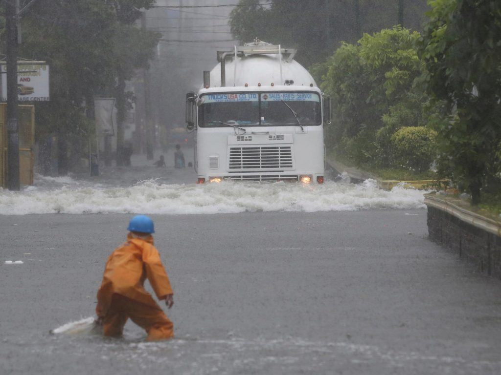 A man battles throught the wind and rain in New Taipei City as Typhoon Megi hits