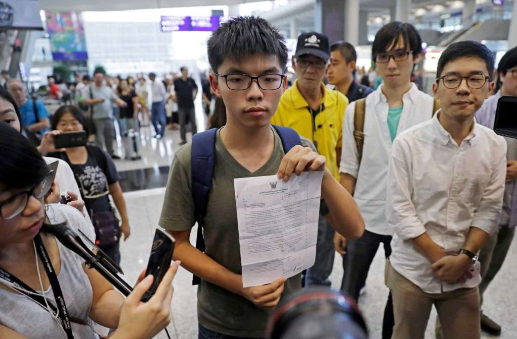 Joshua Wong, center, shows the letter from Thailand Immigration office after arriving at Hong Kong airport from Bangkok.
