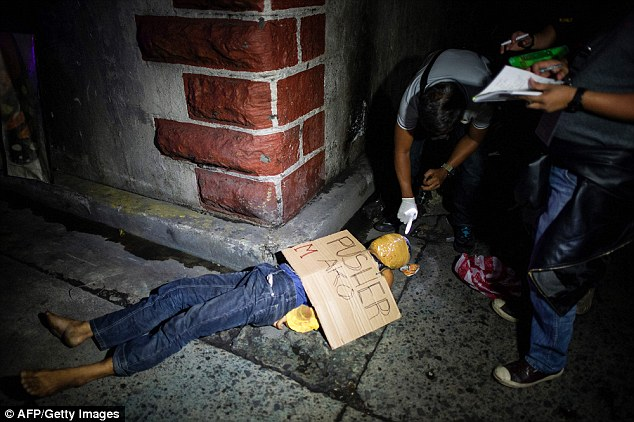 """police officers investigate the dead body of an alleged drug dealer, his face covered with packing tape and a placard reading """"I'm a pusher"""", on a street in Manila"""
