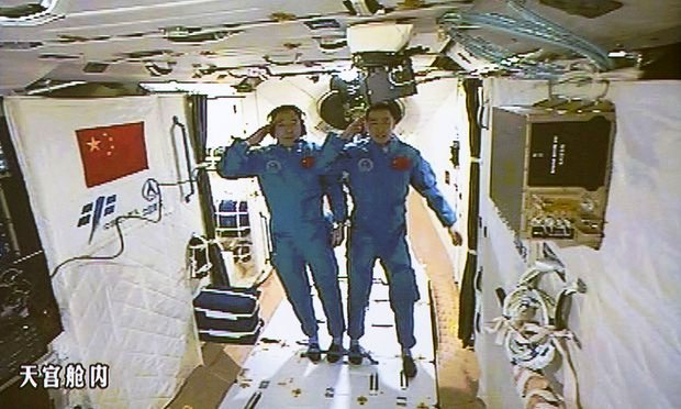 Chinese astronauts Jing Haipeng, left and Chen Dong salute in the space lab Tiangong 2