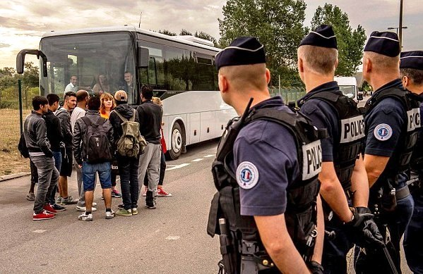 Migrants from the 'Jungle' camp in Calais wait under police surveillance for a bus heading to a 'welcome and orientation centre'
