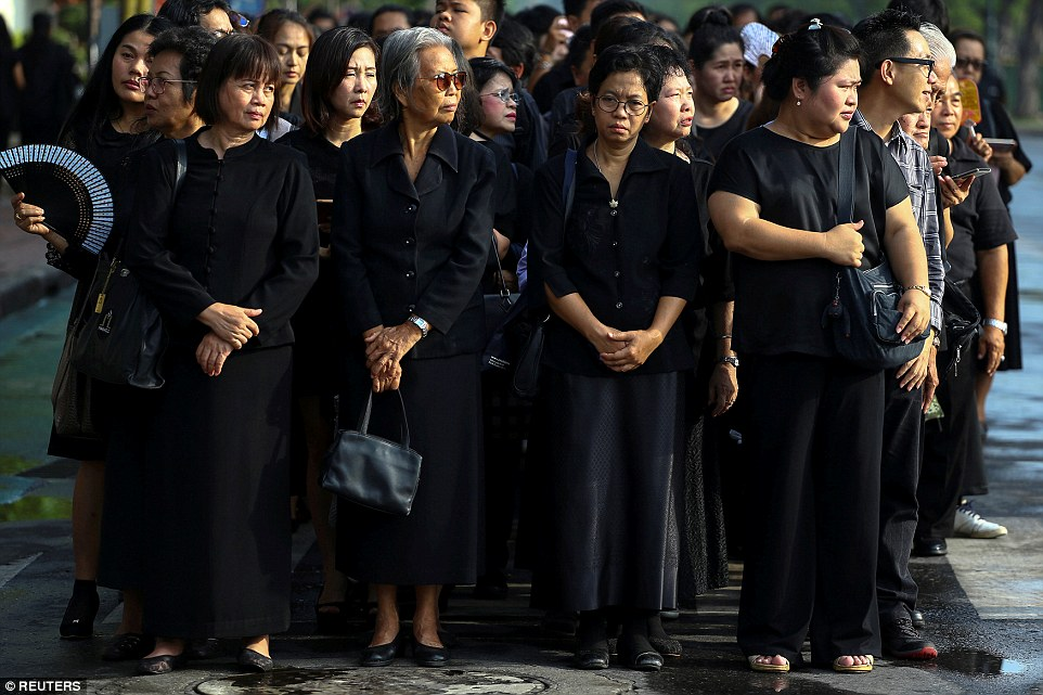 People wear black as they stand in line to offer condolences for Thailand's late King Bhumibol Adulyadej at the Grand Palace in Bangkok - Photo Reuters