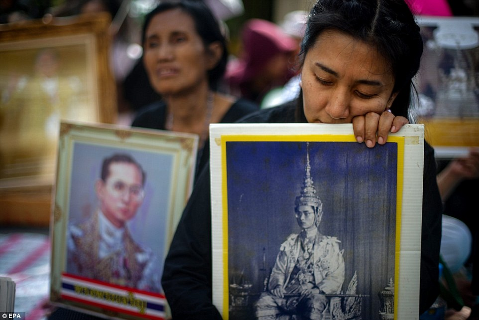 Thai people mourn with portraits of late Thai King Bhumibol Adulyadej ahead of a procession to transport the king's body