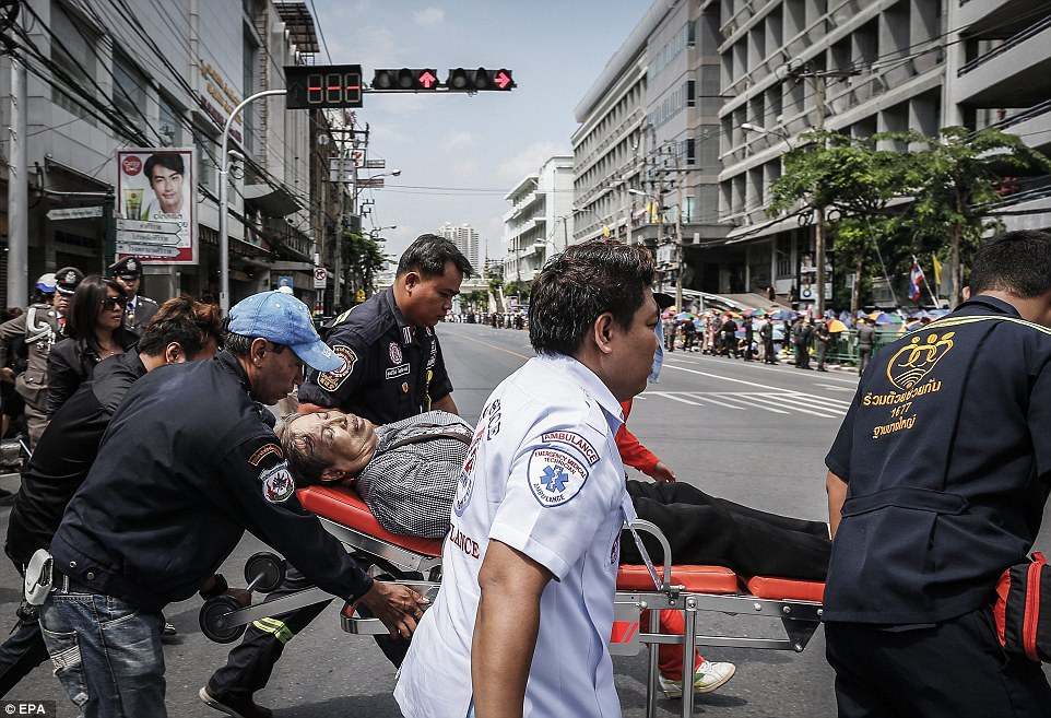 Thai paramedics carry a well-wisher on a stretcher who fainted while waiting for the procession