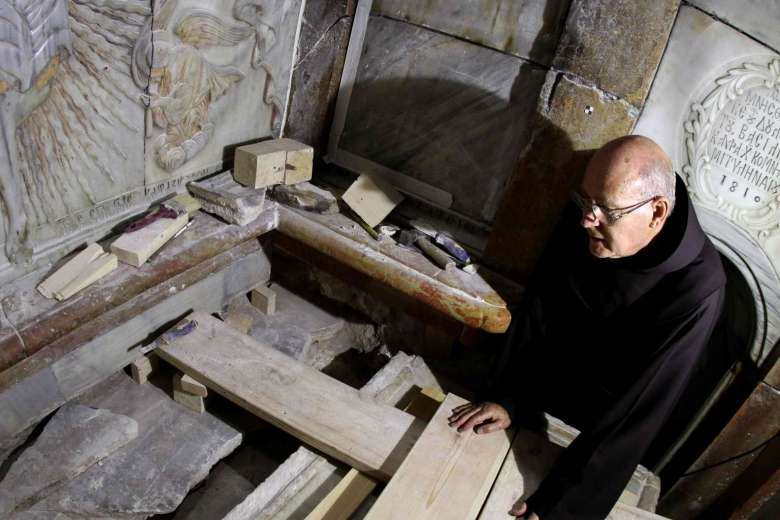 A Franciscan friar looks at the exposed the Tomb of Jesus, where his body is believed to have been laid, as part of conservation work done by a team of Greek team of preservation experts in Jerusalem