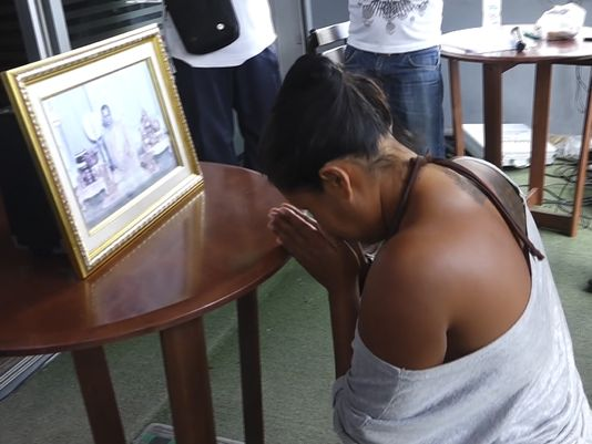 In this image made from video taken on Sunday, Oct. 16, 2016, Umaporn Sarasat, 43, pays respects in front of a portrait of Thailand's King Bhumibol Adulyadej in Koh Samui, Thailand. She is accused of insulting the country's late king and was forced to kneel before his portrait outside a police station on the tourist island of Samui as several hundred people bayed for an apology.(Photo: AP)