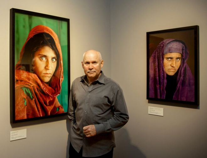 """US photographer Steve McCurry poses next to his photos of the """"Afghan Girl"""" Sharbat"""
