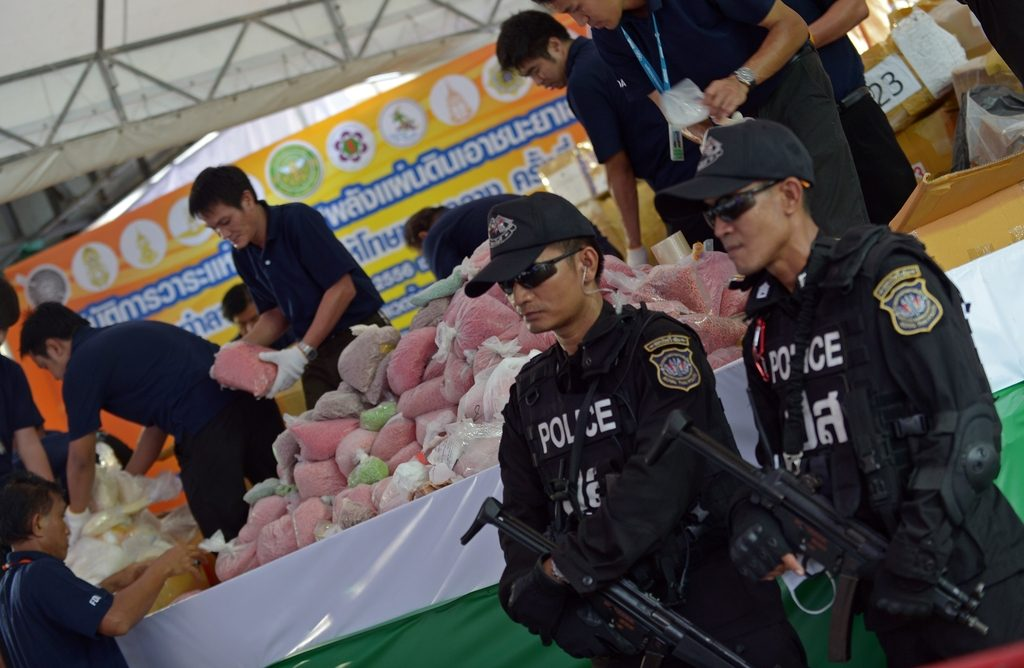 A Thai commando unit stand guard in front of packs confiscated narcotics before destroying them marking the UN's International Day Against Drug Abuse and Illicit Trafficking in Ayutthaya province