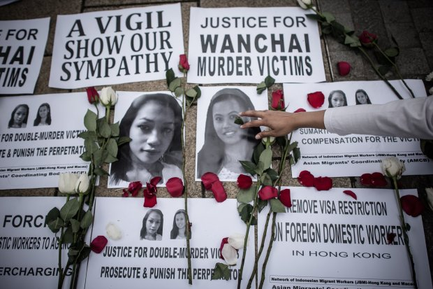 An Indonesian migrant worker lays rose pertals over the pictures of murder victims in Hong Kong on November 9, 2014.  British banker Rurik Jutting, 29, has been charged with murdering Indonesians Sumarti Ningsih and Seneng Mujiasih after police found their mutilated bodies in his upmarket Hong Kong apartment on November 1.     AFP PHOTO / Philippe Lopez        (Photo credit should read PHILIPPE LOPEZ/AFP/Getty Images)