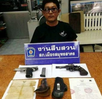Suchaet Muangsamut is pictured Friday alongside the two guns he displayed in a Facebook video he posted Wednesday, in which he threatened to kill anyone defaming the Late King Bhumibol in Samut Sakhon