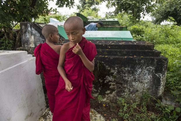 Cemetery personnel bury the body of three-year-old Nay La Linn, a victim of an exorcism ritual, in Twante town, south of Yangon on Saturtday as novice monks look on (AFP Photo)