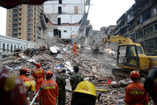 Rescue workers search at the site where residential buildings collapsed in Wenzhou, Zhejiang province, China, October 10, 2016. REUTERS/Stringer ATTENTION EDITORS - THIS IMAGE WAS PROVIDED BY A THIRD PARTY. EDITORIAL USE ONLY. CHINA OUT. NO COMMERCIAL OR EDITORIAL SALES IN CHINA.