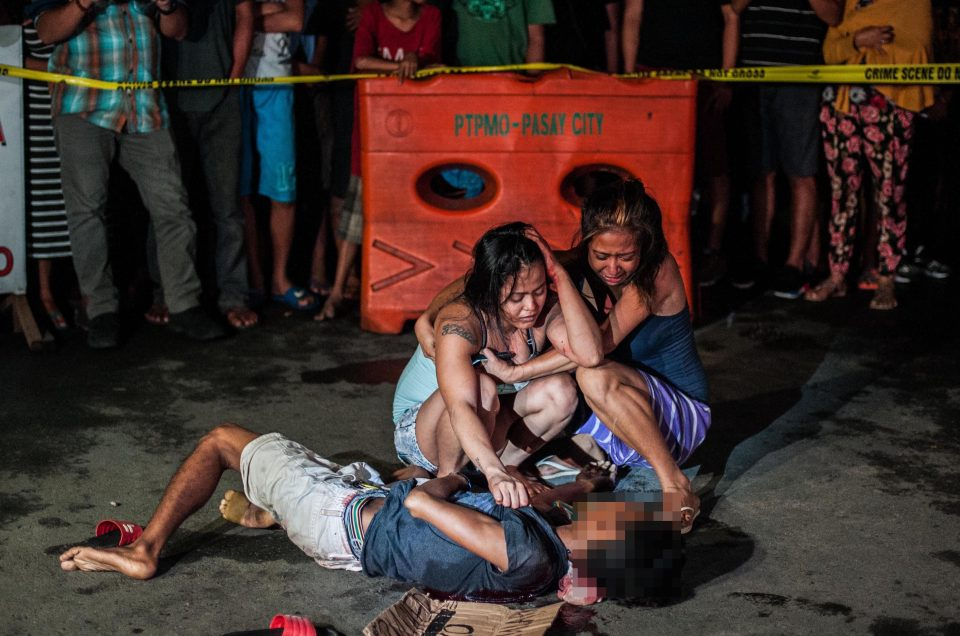 Distraught relatives stand over the body of their slain loved one reportedly murdered for being a drug dealer