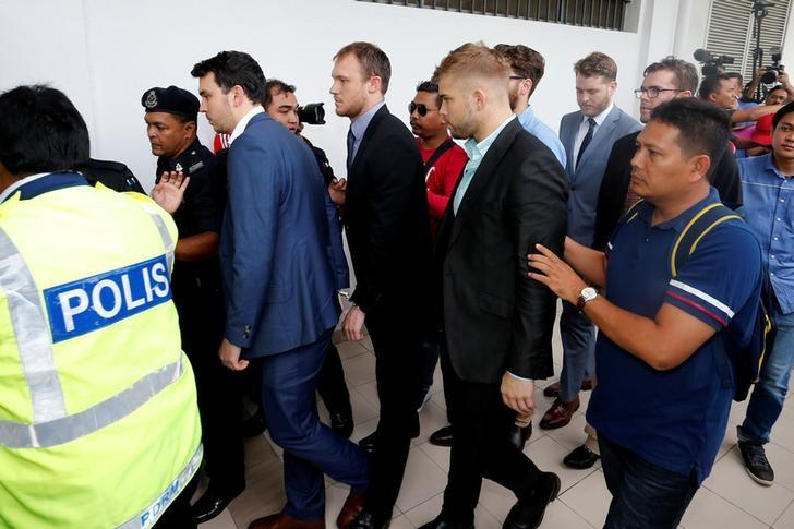 Australian men, part of a group of nine who were detained for stripping down to their underwear at last Sunday's Formula One Malaysian Grand Prix, are escorted as they arrive at the Magistrate Court in Sepang, Malaysia.