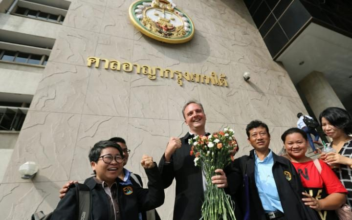 British lawyer and migrant workers' rights activist, Andy Hall (C) poses for a photo with supporters as he arrives for his trial at the Bangkok South Criminal Court in Bangkok, Thailand.  Credit: EPA/NARONG SANGNAK