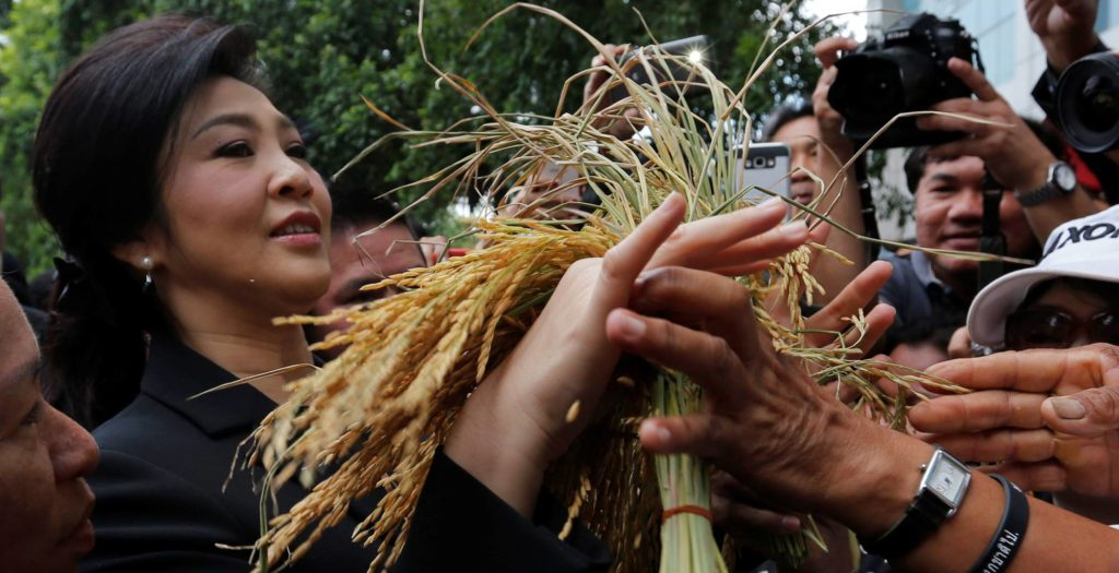 Thai Prime Minister Yingluck Shinawatra receives a sheaf of rice from supporters outside court in Bangkok on Friday. She could be set to prison for up to 10 years if convicted of mishandling a multibillion-dollar rice-subsidy program. Photo: Chaiwat Subprasom/Reuters