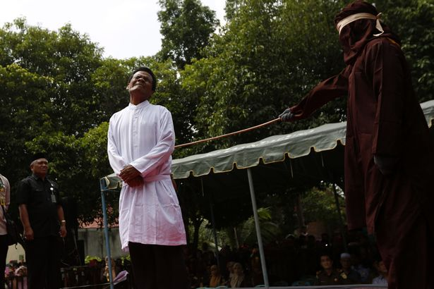 A man grimaces as he is whipped for having sex outside marriage (Photo: EPA)