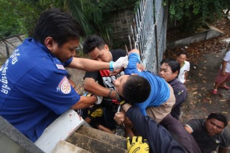 Passers-by held the boy steady to take some weigh off his injury - Photo Natarit Noonpradate
