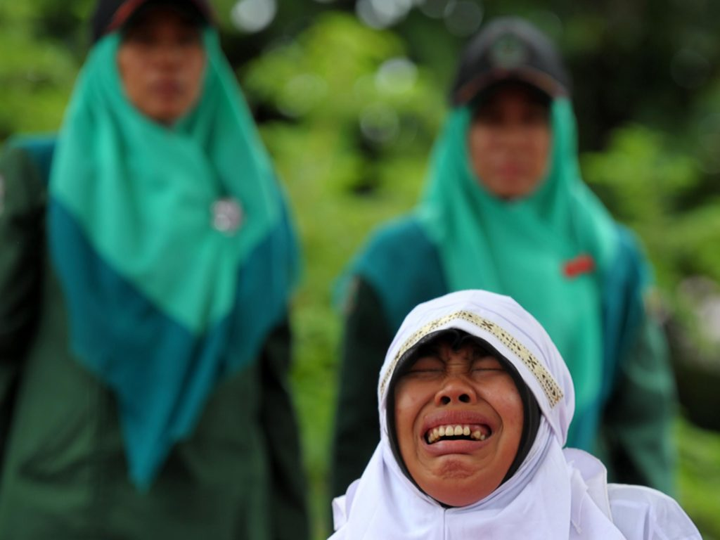 A woman cries as she is hit 23 times with a cane for spending time with her boyfriend in Banda Aceh, Indonesia AFP