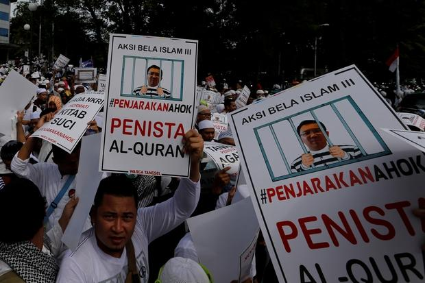 Muslims hold up posters during a rally calling for the arrest of Jakarta Governor Basuki Tjahaja Purnama, popularly known as Ahok, who is accused of insulting the Koran