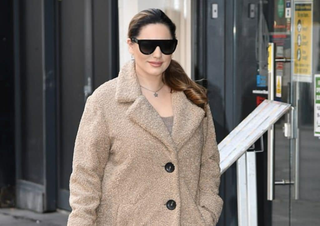 Kelly Brook bundles up in a light brown teddy bear coat and jeans