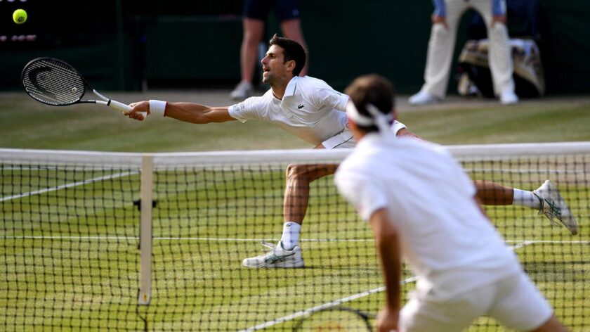 Djokovic stretches to play a forehand against Federer.