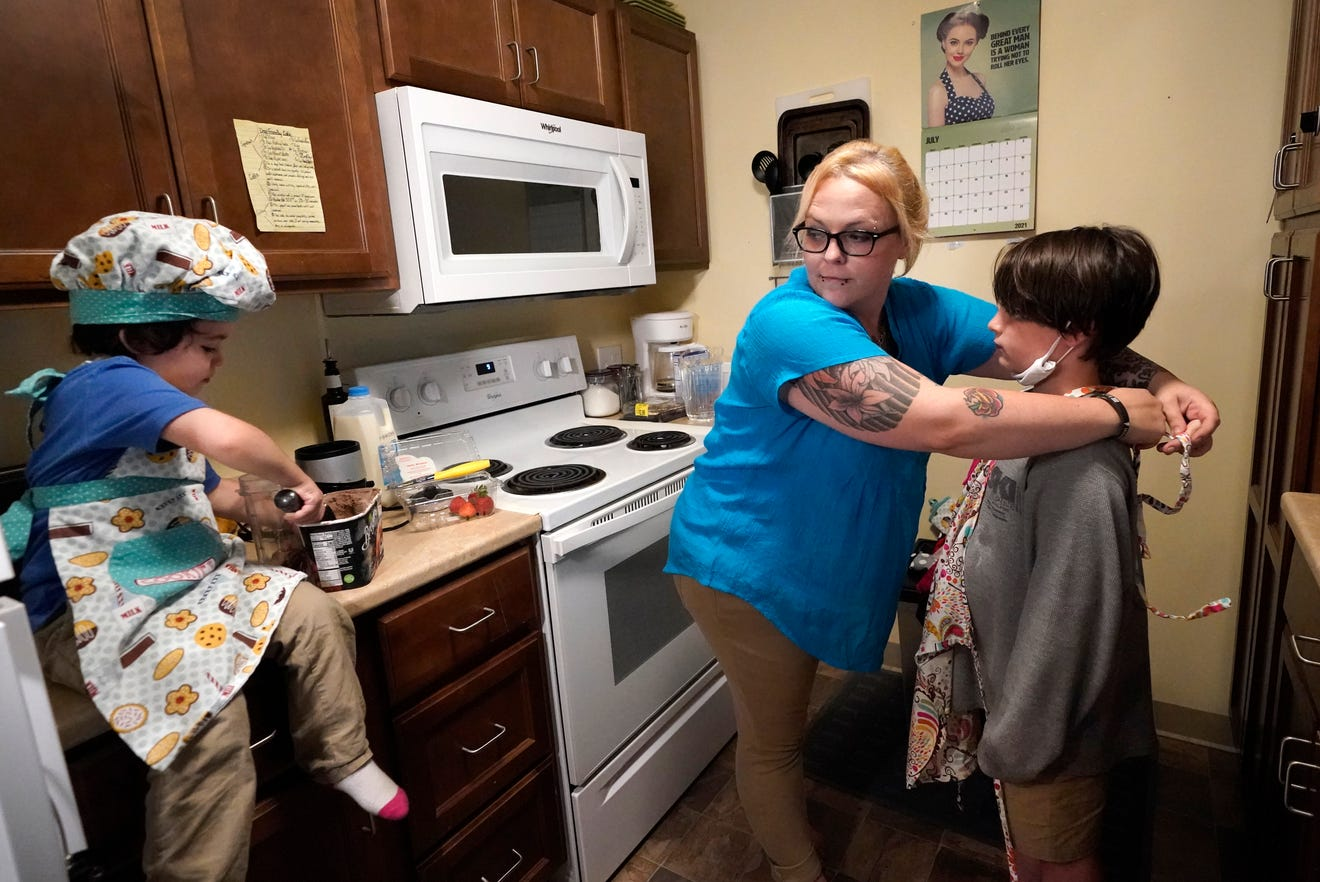 """data-c-caption=""""In this July 28, 2021 photo, Christina Darling and her sons, Brennan, 4, left, and Kayden, 10, prepare a snack at home in Nashua, N.H. Darling and her family have qualified for the expanded child tax credit, part of President Joe Biden's $1.9 trillion coronavirus relief package. Darling is a housing resource coordinator who had been supplementing her $35,000-a-year salary with monthly visits to the Nashua Soup Kitchen and Shelter's food pantry. (AP Photo/Elise Amendola) ORG XMIT: NHEA202"""""""