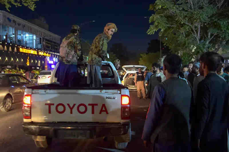 Taliban fighters stand on a pickup truck outside a hospital as volunteers bring injured people for treatment after two powerful explosions outside the airport in Kabul.