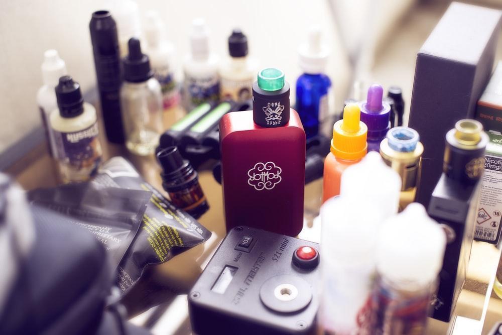 red box mod vape beside e-juice bottles